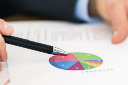 Kugelschreiber zeigt auf Blatt mit Statistiken